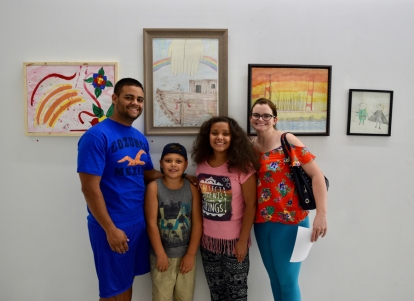Family stands in front of their new art work purchased at the MNA Exhibition 2017